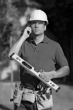 building contractor with tools and cell phone