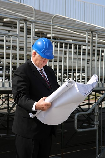 contractor examining blueprints at a construction site